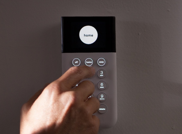 Hand about to press button on keypad displaying the word 'home' in a white circle