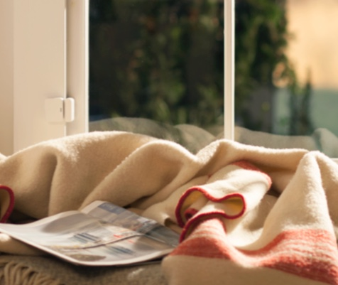 Magazine on top of brown blanket with glass door in background